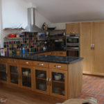 Kitchen units double sided with glass doors and granite tops, shelves in the background on invisible fixings
