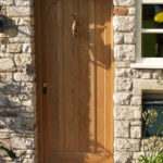 arched oak door with dolphin knocker