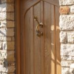 Closer view of arched door in oak with a beautiful dolphin knocker