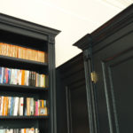 lion carvings on black painted bookcase
