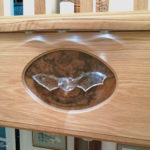 carving of bat set in cocobola veneer panel set in oak with lights