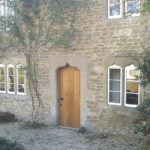 door in oak with arched top in wellow bath from a distance