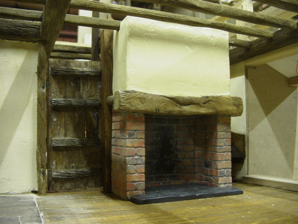 Model fireplace with bricks scratched into plaster, also distressed oak door to the side
